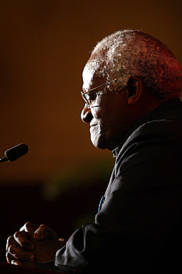 Photo of Desmond Tutu seated with hands folded in front of him. He seems to be in prayer.