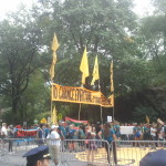 """Marchers hold a large yellow banner with the text: """"""""To change everything, we need everyone."""""""