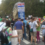 """In center frame is the back of a 9-foot tall puppet of Exxon CEO Rex Tillerson. The sign reads """"Exxon CEO Rex Tillerson says 'Why save the planet?''"""