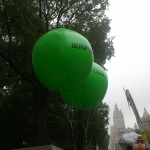 """Two large green balloons float among the trees with the text """"Disrupt"""" and """"Denial"""" on them."""