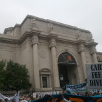 A mix of people and anti-capitalist banners outside the Natural History Museum