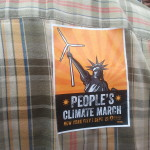 Back of an orange-brown plaid shirt with an orange People's Climate March sticker in the center.