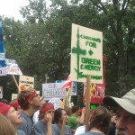 """Marchers look up at something in the sky o-screen. Signs read """"Canadians for Green Energy Investment."""""""