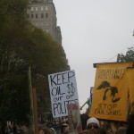 """A white handwritten protest sign: """"Keep Oil $$ out of politics."""" To the right, a man from the Canadian group holds a yellow sign: """"Great Lakes Resistance. Stop Tar Sands."""""""