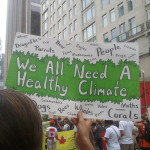 """A green and white hand-lettered sign reads """"We all need a healthy climate."""" The word """"People"""" and the names of non-human species surround this text."""