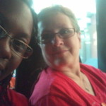 We take a quick photo on the bus home. Both wear red shirts for the section of the March we were in.
