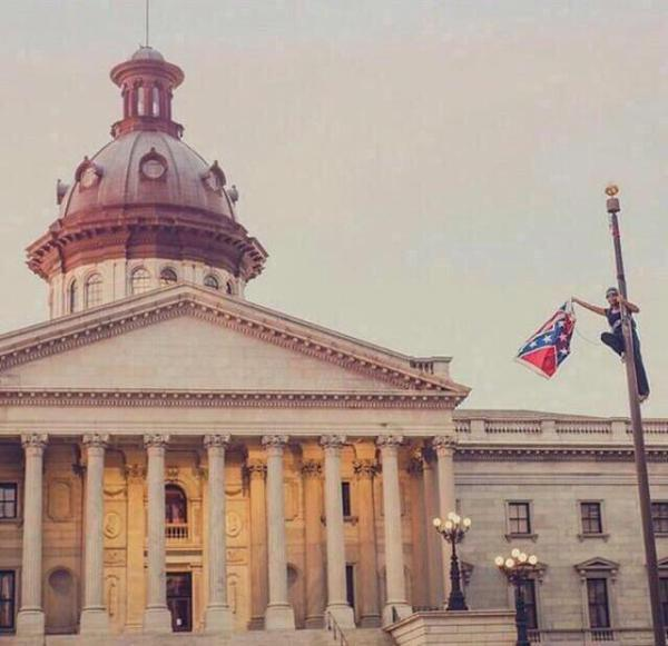 Bree Newsome waves the Confederate battle flag while on the flagpole outside the South Carolina state capitol building. Photo via @Bipartisanism.