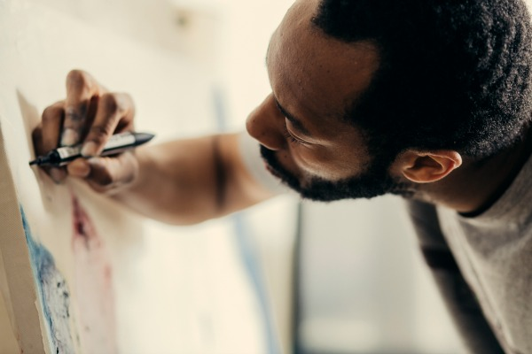 A black man with close cropped hair and full beard draws on a canvas or paper with a marker. Photo credit: Death to the Stock Photo. Used under license.