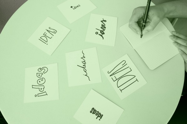 "A person writes ""Ideas"" in different script styles. Only their hand is visible in the top right corner of the photo."