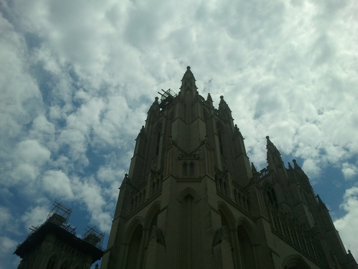The camera looks up at a tower of the National Cathedral, Washington, D.C. The tower is scaffolded for repairs. In the background a deep blue sky is filled with white, fluffy clouds. The tower is in shadow. Photo by Keisha E. McKenzie.