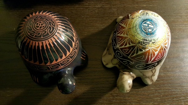 Two ceramic turtles viewed from above a dark brown wooden surface. On the left is red clay in the shape of a turtle, etched, and glazed in black. To the right is white with black horsehair pattern and rainbow-glazed etchings for the shell.