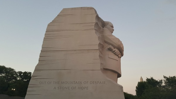 Side view of the MLK Memorial, Washington, D.C. The sky is a light blue with sunset colors toward the base of the photo. It is evening.