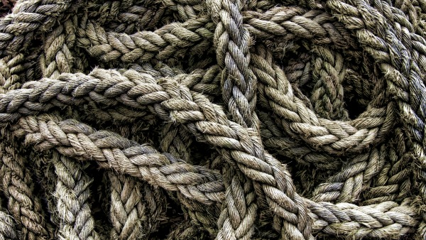 A close-up photo of a wide grey rope tangled on the floor.
