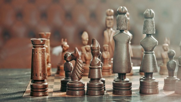 A close up of human-like chess peoples on the board. The background is blurry; the foreground is crisp.