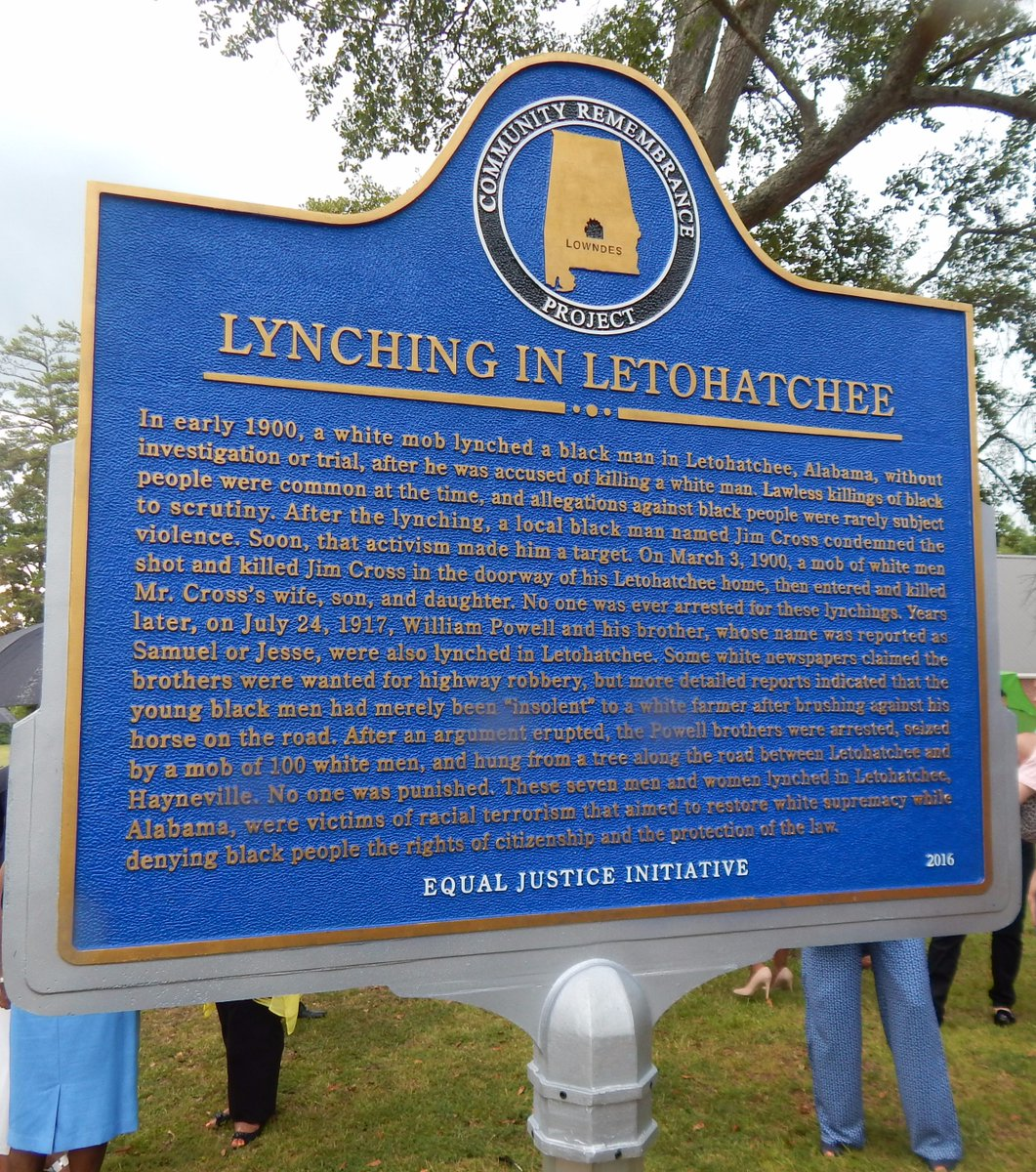 """A royal blue historical marker, likely made out of metal, reads """"Lynching in Letohatchee"""" in capital letters. """"Equal Justice Institute"""" is in white capitals at the bottom of the marker. In the background are grass and tree branches. People's legs are visible toward the edges of the photo."""