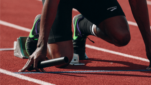 Zoomed in photo of a Black relay runner crouching and ready to launch off the starting blocks. They are in black fitted running shorts and Nike sneakers
