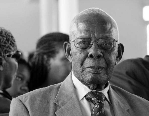 An elderly dark-skinned Black man with closely cropped white hair sits in a church looking directly into the camera. He wears a light colored suit with a darker patterned tie and a white or light-colored shirt. His facial expression holds a slight smile. His mouth is closed. He is wearing rounded glasses. In the background, blurry, are other people, women and a young girl.