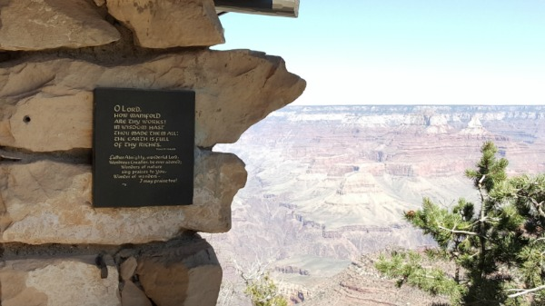 A paint-lettered wooden plaque mounted on the stone wall, overlooking the brightly lit South Rim, Grand Canyon.