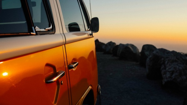 A shiny orange VW van parks on the edge of a cliff at sunset.