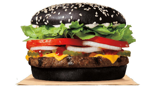 A black sesame burger bun filled with regular colored burger and toppings.
