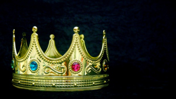 On a black velvet background, a large gold seven-point crown with blue and pink gems inset. The crown is to the far left of the image.