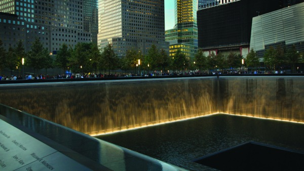 Photo of one of the National 9/11 Memorial voids lit for the evening. Victim names are visible.