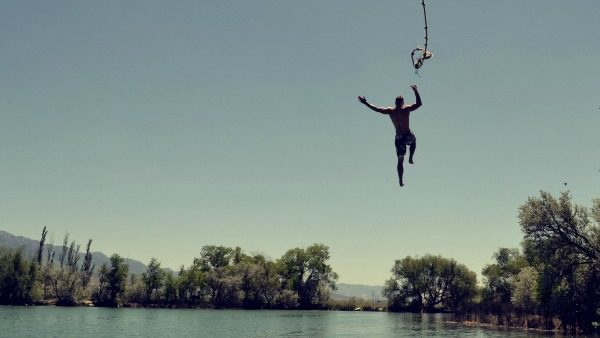 Muscular man jumps into a lake. The rope is visible at the top of the image. The sky in the background is large and blue.