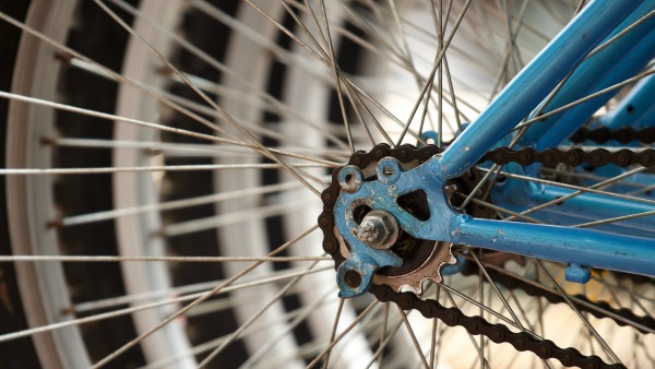 A close-up of a bicycle wheel. The frame is light blue, and the spokes fill the left half of the frame. The chain looks a little rusty.