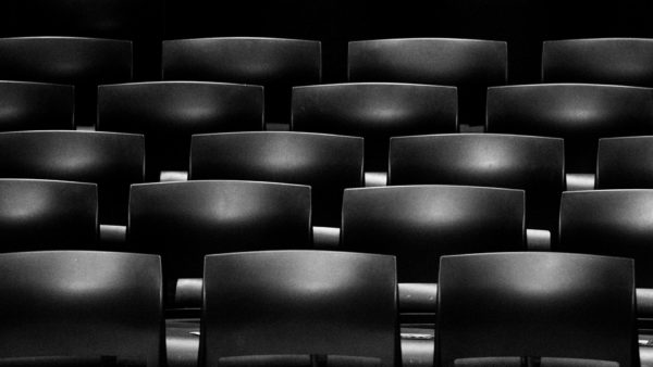 High contrast edit of theater seating photo by Elijah Flores. These seats are all black. The light source is above and in front of them.
