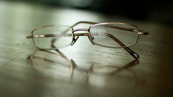 A metal-framed pair of oval glasses sits on a wooden table. There are deep shadows in the background.