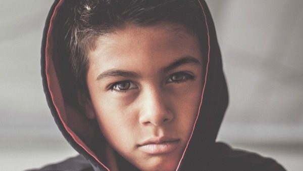 A young boy in a black hoodie stares into the camera.