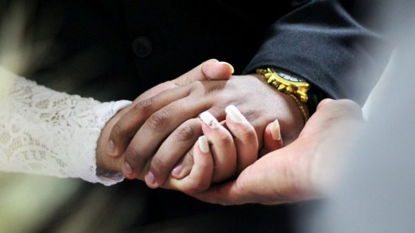 A couple mid-wedding holds hands.