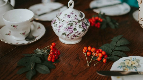 A dark brown table with red berries garnishing the surface around floral white teapot and cups and saucers.