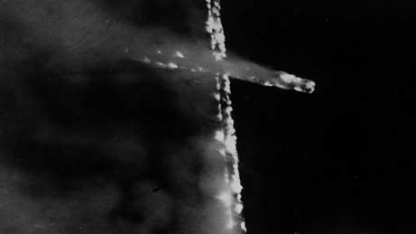 A burning cross bisects this image. The background is deep grey-to-black on the right; on the left, lighter grey smoke billows around the arms of the cross. Via Wikimedia Commons.