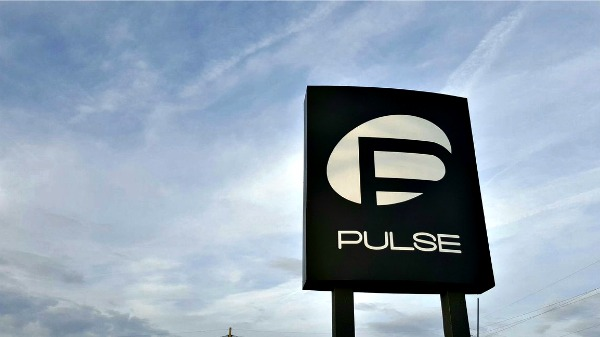 The street sign of the Pulse night club, Orlando, Florida. The sign is deep black with backlit name and an oval field around the P. The sky is blue with wispy clouds. Photo credit: Keisha E. McKenzie