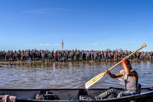 A man holds an oar in the air on the Missouri River: a thick line of water protectors line the banks of the river.
