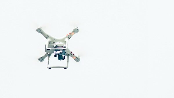 On a white-blue background, a white four-armed photo drone hangs in the sky.