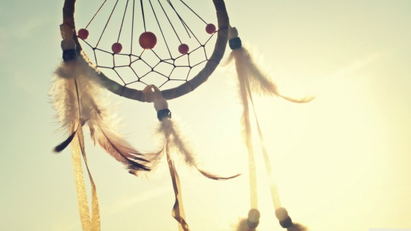 A dream catcher flies in the air. The sky behind it is light blue. There's a sun flare in the center of the image.