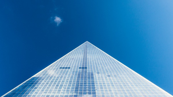 A glass pyramid photographed with a bright blue almost cloudless sky.
