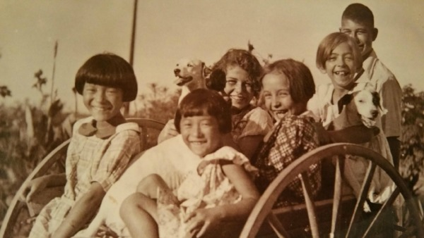 Six children—two Japanese, four White American—sit smiling in a large-wheeled wagon. The girls are wearing tunic dresses. The boy stands behind the wagon. Two girls are holding dogs in their arms.