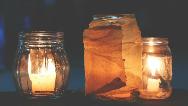 Two candles in short glass jars. Foreground is an orange hue; background is dark blue.