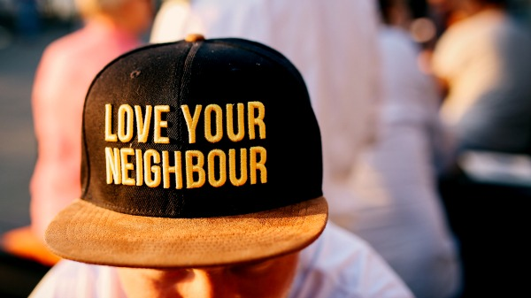 A young light-skinned man leans toward the camera. He is out of focus. In sharp focus is his baseball cap, which reads 'Love your neighbour.'