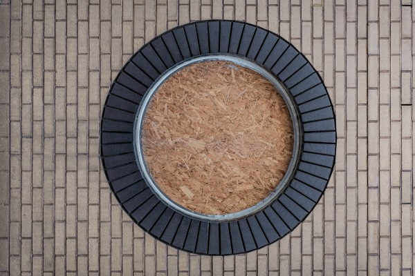 View of a round paved space. Tan bricks and black stone.