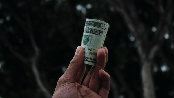 A hand holds up a roll of $20 bills.