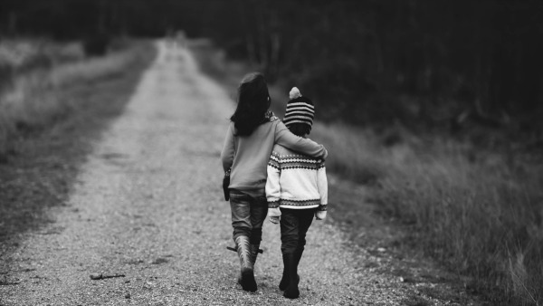 two children walk away from the camera on a gravel path. The taller has their arm around the shorter. The shorter has their hands by their sides.