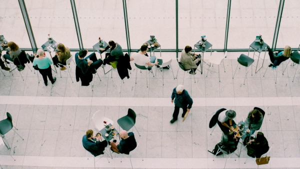 From above, clusters of people sit around round tables in a brightly light and white-tiled atrium.