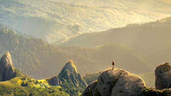 Low golden sunlight washes over a rocky and grassy mountainous landscape. A solitary figure stands on a rocky outcrop on the bottom right of the image. They are facing away from the camera.