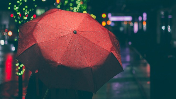 A red dotted umbrella fills much of the frame. Blurred in the background is a night-time urban scene.