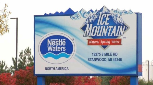 A roadside billboard ad features Nestlé's Ice Mountain spring water bottling plant. Trees below the ad are orange and red.