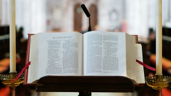 A bible on a podium; background is out of focus; appears to be a church.